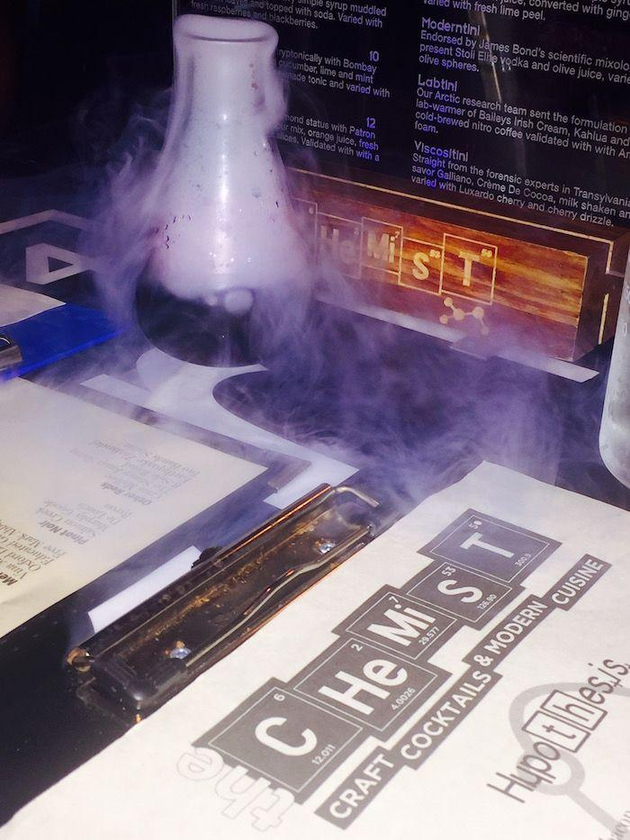The Chemist menu and a smoking cocktail in a beaker