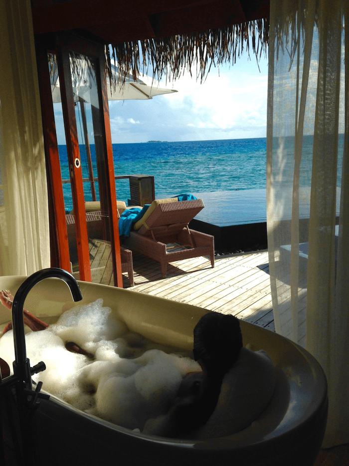 woman taking bubble bath in front of open doors to the ocean