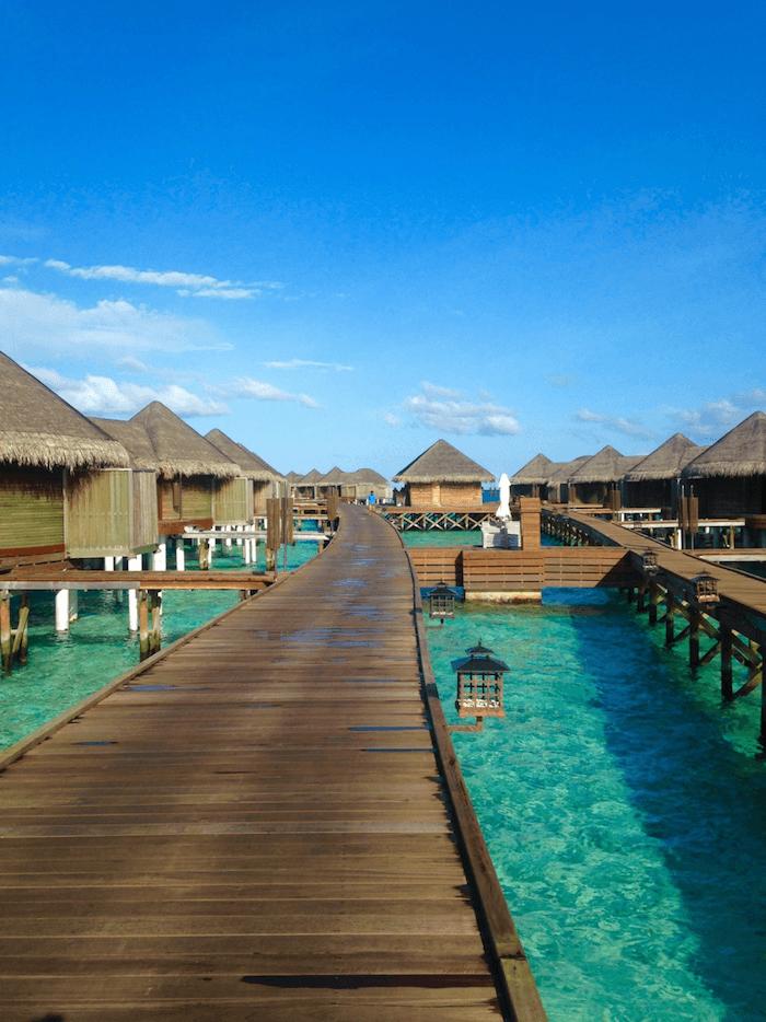 wooden walkway pier to water villas