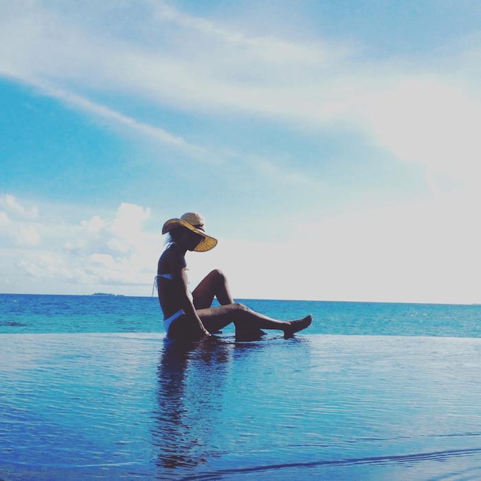 woman at edge of infinity pool overlooking ocean
