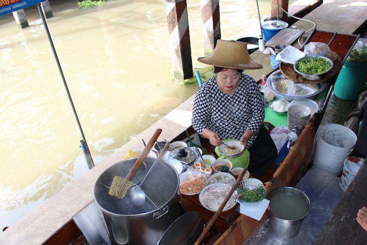 Thai woman cooking noodles for sale