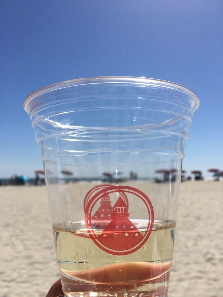 a plastic cup filled with Prosecco with the beach in background