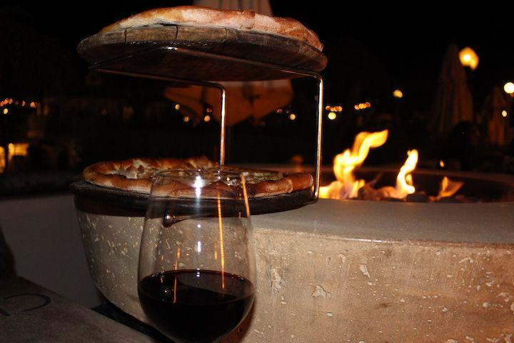 pizzas on a pizza stand by a fire pit