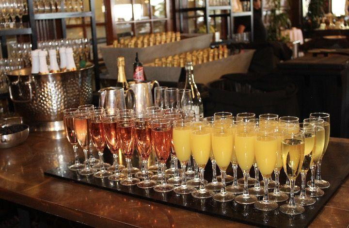 A tray of glasses filled with wine and mimosas