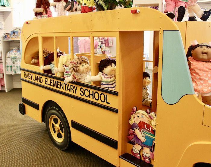 Cabbage Patch Kids riding a wooden school bus