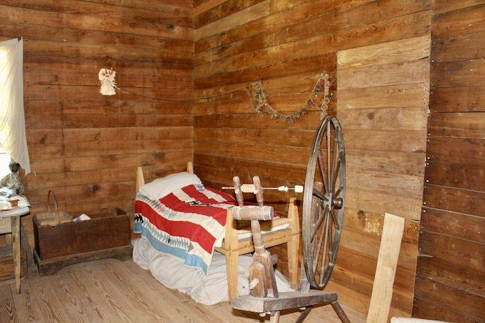 a bed and spinning wheel inside the slave cabin
