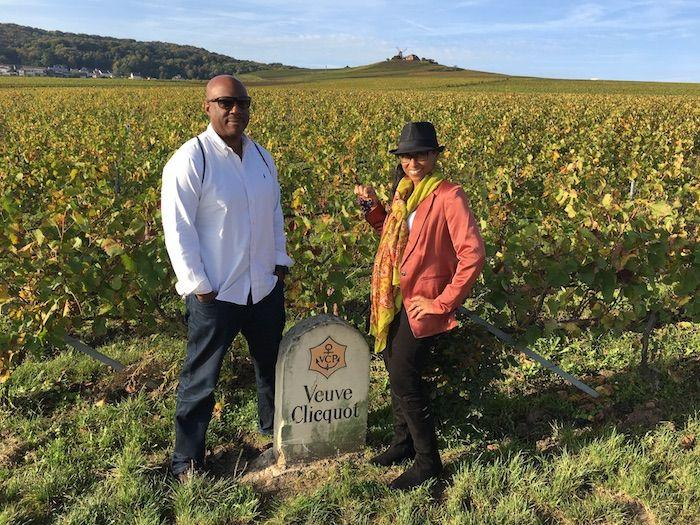 the author and her husband in a winery by a Veuve Clicquot sign