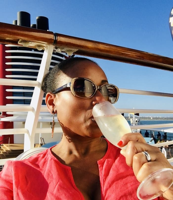 woman drinking champagne on the deck of a cruise ship