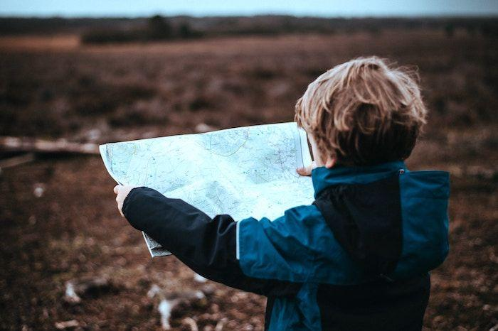 young male child holding map
