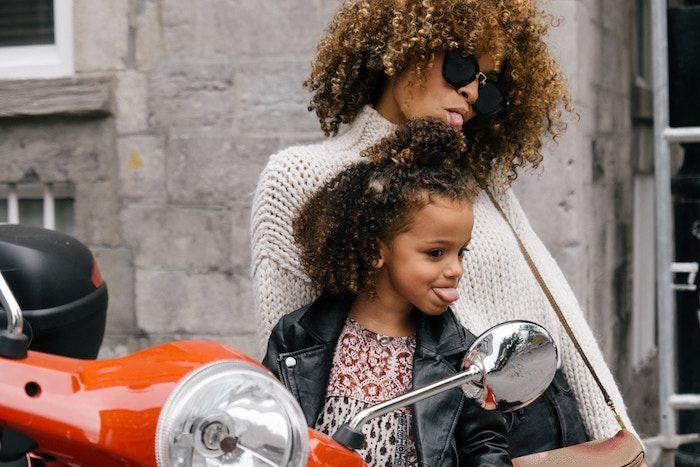 woman and female child on motor bike sticking out tongues