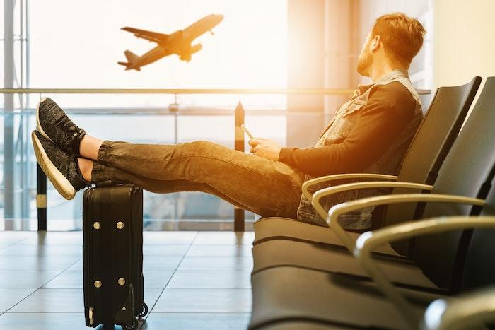 male traveler at airport watching plane take off