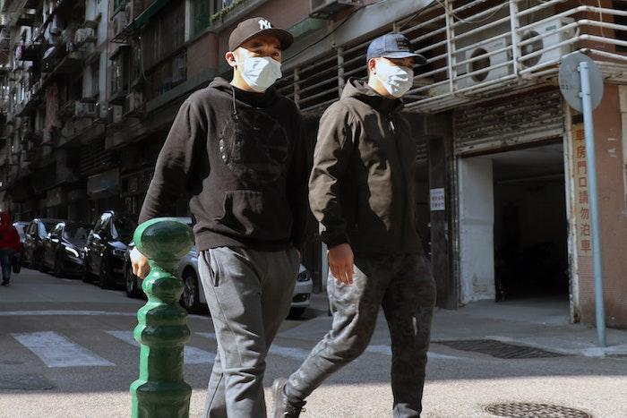 two men wearing face masks on the street