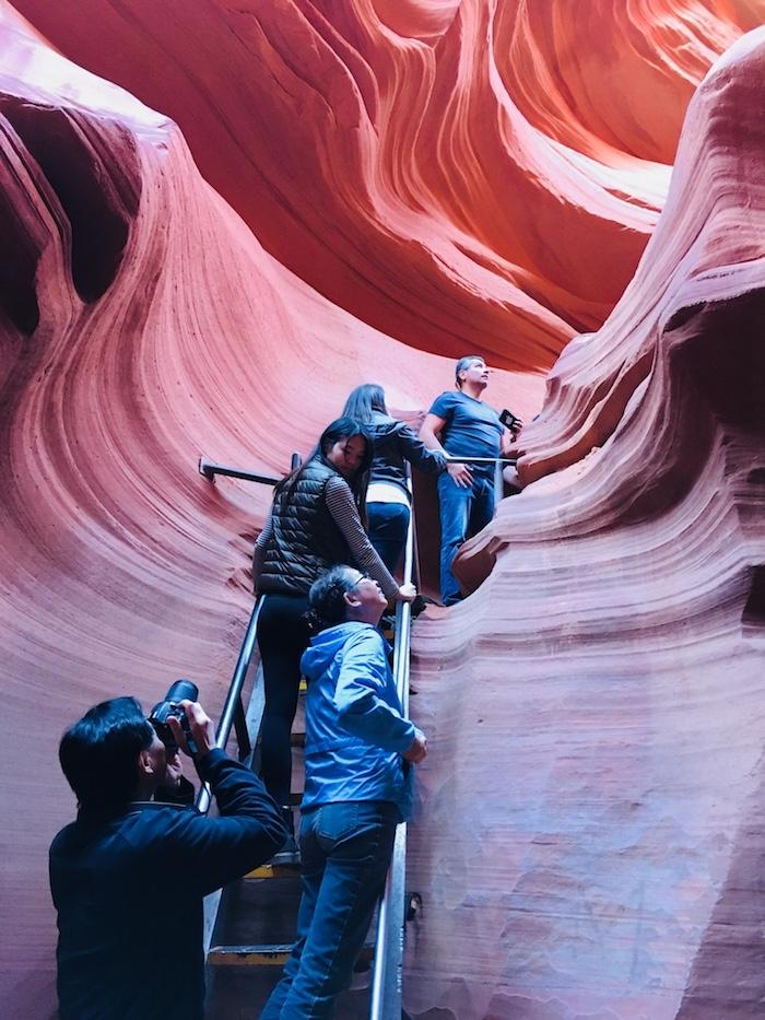 people climbing up a ladder in Lower Antelope Canyon