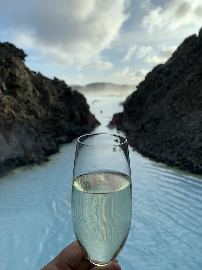 a glass of champagne held up against the Blue Lagoon