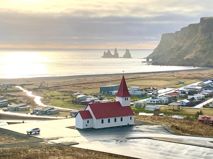 a church in Vik with a red roof and steeple overlooking the water