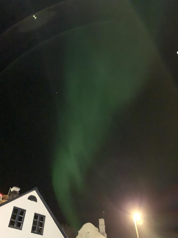 the northern lights above Reykjavik houses