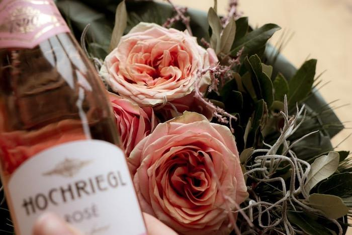 bottle of rosé wine next to pink roses