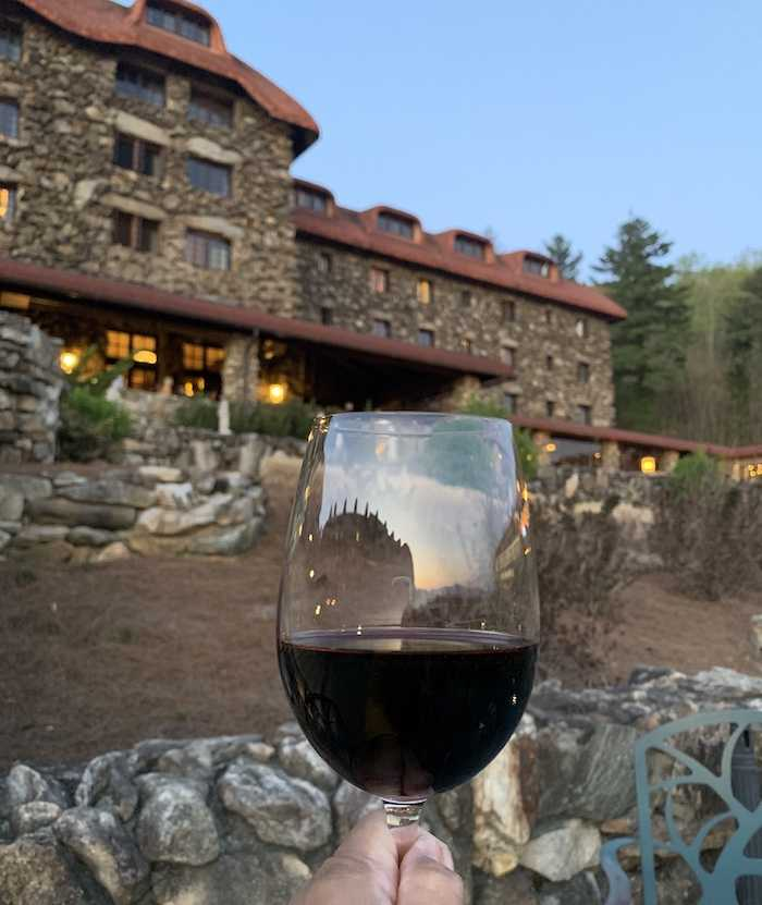filled wine glass with The Omni Grove Park Inn in the background
